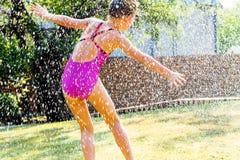 Маленькая девочка имея потеху под падениями воды Стоковое фото RF