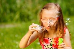 Маленькая девочка имея пузыри мыла потехи дуя в парке Стоковые Изображения RF