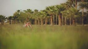 Маленькая девочка использует smartphone на зеленой лужайке с пальмами сток-видео