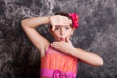 Маленькая девочка используя руки для того чтобы обрамить ее сторону Стоковая Фотография RF