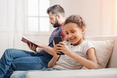 Маленькая девочка используя smartphone пока книга чтения отца на софе Стоковое Изображение
