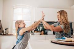 Маленькая девочка и ее мать в кухне давая максимум 5 Стоковое фото RF