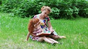 Маленькая девочка и ее мать прочитали книгу на лужайке в зеленом парке лета сток-видео