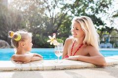 Маленькая девочка и ее мать с коктеилем в тропическом бассейне пляжа стоковое изображение rf