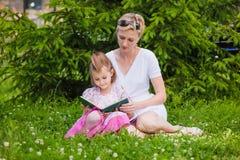 Маленькая девочка и ее мать читая книгу Стоковое Изображение RF