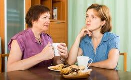 Маленькая девочка и ее постаретый кофе матери выпивая Стоковые Фото