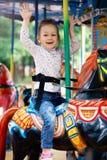 Маленькая девочка идет для привода на carousel Стоковые Фотографии RF