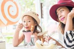 Маленькая девочка и мать есть мороженое Стоковые Изображения RF