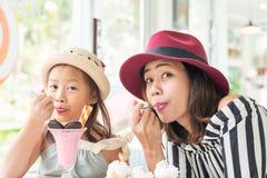 Маленькая девочка и мать есть мороженое Стоковое Изображение