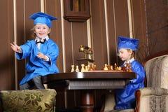 Маленькая девочка и мальчик в голубых костюмах играют шахмат Стоковая Фотография
