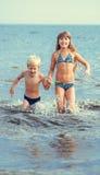Маленькая девочка и мальчик в море стоковое фото rf