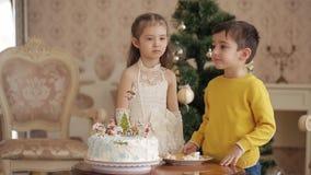 Маленькая девочка и мальчик есть торт на предпосылке рождественской елки Большая живущая комната с рождественской елкой видеоматериал