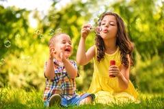 Маленькая девочка и мальчик играя с пузырями мыла Стоковая Фотография