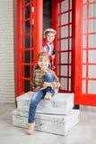 Маленькая девочка и мальчик около переговорной будки Стоковые Фото