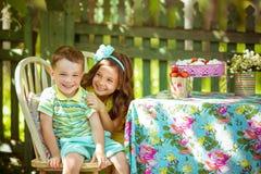Маленькая девочка и мальчик сидят и усмехаются на таблице в саде Стоковые Фотографии RF