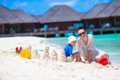 Маленькая девочка и молодая мама играя с пляжем забавляются Стоковая Фотография RF