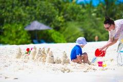 Маленькая девочка и молодая мама играя с пляжем забавляются Стоковое Изображение