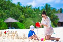 Маленькая девочка и молодая мама играя с пляжем забавляются Стоковая Фотография