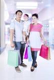 Маленькая девочка и родители ходя по магазинам на моле Стоковое фото RF