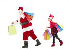 маленькая девочка и Санта Клаус держа хозяйственные сумки Стоковые Фото