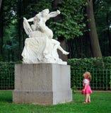 Маленькая девочка и скульптура стоковое фото rf
