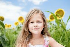 Маленькая девочка и солнцецветы в летнем дне Стоковое Изображение