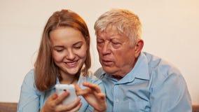 Маленькая девочка и старый человек учат Smartphone видеоматериал