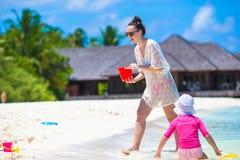 Маленькая девочка и счастливая мать играя с пляжем Стоковое Фото