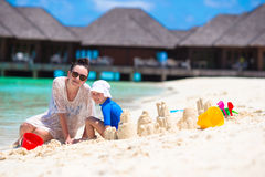 Маленькая девочка и счастливая мать играя с пляжем Стоковая Фотография