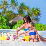 Маленькая девочка и счастливая мать играя с пляжем Стоковые Фотографии RF