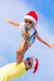 Маленькая девочка и счастливый папа в шляпе Санты во время пляжа отдыхают стоковое изображение