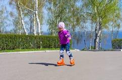 Маленькая девочка катаясь на коньках на коньках ролика Стоковая Фотография
