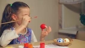 Маленькая девочка красит пасхальные яйца видеоматериал