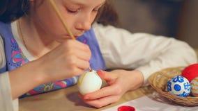 Маленькая девочка красит пасхальные яйца акции видеоматериалы