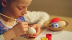 Маленькая девочка красит пасхальные яйца сток-видео