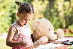 Маленькая девочка крася внешней с ее другом плюшевого медвежонка Стоковое Фото
