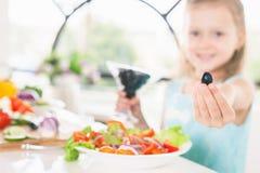 Маленькая девочка крупного плана милая делая салат Держать оливку Варить ребенка Стоковое Изображение RF