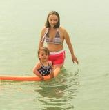 Маленькая девочка купая с ее матерью в море Стоковые Изображения