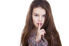 Маленькая девочка клала forefinger к губам как знак безмолвия Стоковые Изображения