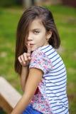 Маленькая девочка клала forefinger к губам как знак безмолвия Стоковое фото RF