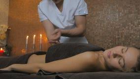 Маленькая девочка кладя на таблицу и наслаждается массажем в курорте сток-видео