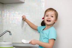 Маленькая девочка моет блюда Стоковые Изображения RF