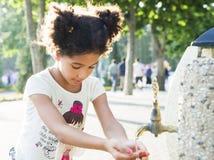 Маленькая девочка моет ее руки на кране Стоковые Изображения RF