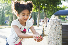 Маленькая девочка моет ее руки на кране Стоковое Фото