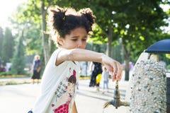 Маленькая девочка моет ее руки на кране Стоковое Изображение