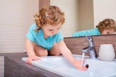 Маленькая девочка моя ее руки в ванной комнате Стоковое фото RF