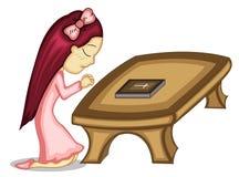 Маленькая девочка моля с библией на таблице Стоковое Изображение RF