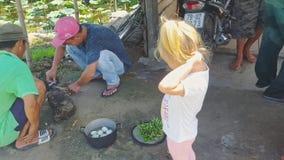 Маленькая девочка наблюдает въетнамскими людьми для того чтобы сделать огонь сток-видео