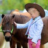 Маленькая девочка наслаждаясь ее пони Стоковые Фото