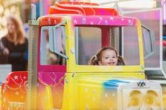 Маленькая девочка наслаждаясь ездой ярмарки потехи, парком атракционов стоковые фотографии rf